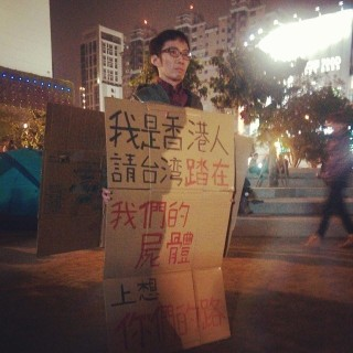 "A resident of Hong Kong supports the Sunflower Movement, holding a sign that says, ""I am from Hong Kong. People of Taiwan, please step on our corpses as you think about what path you will take forward."""
