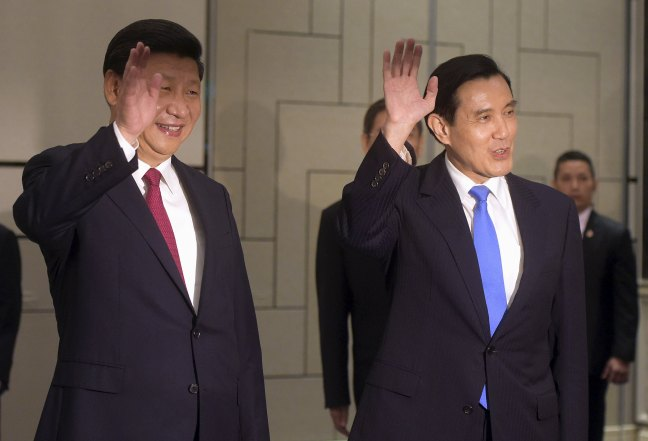 Chinese President Xi Jinping and Taiwanese President Ma Ying-jeou wave to photographers as they enter the room at the Shangri-la Hotel where they are to meet, in Singapore